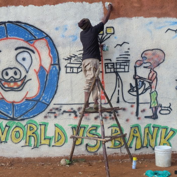 Activists in Nairobi graphiti a wall with a message for the World Bank
